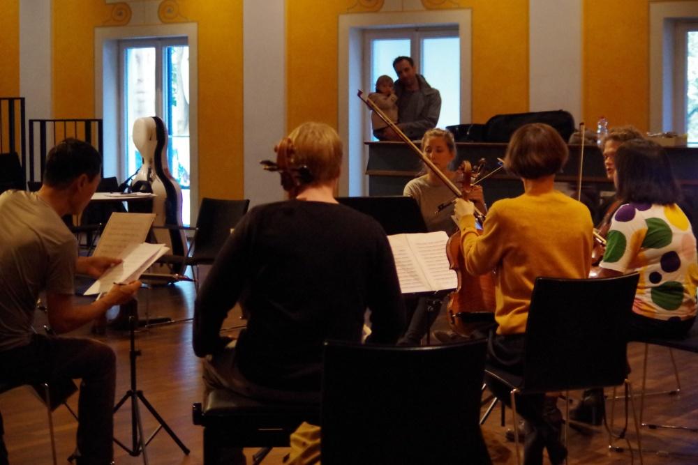 25.9.2018 – Proben: ... Bassist und Papa Olivier Thiery mit Nachwuchs beobachten, was die Mama Lilli Maijala (Viola 2) da so macht ... (Foto: Christine Tröger)